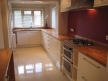 Replanned and redesigned cream and oak kitchen with porcelain floor tiles.