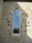 A new stairwell window is given an impressive arched stone head.