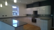 Large modern white high gloss kitchen with Silestone worktop, integrated appliances and separate utility room.